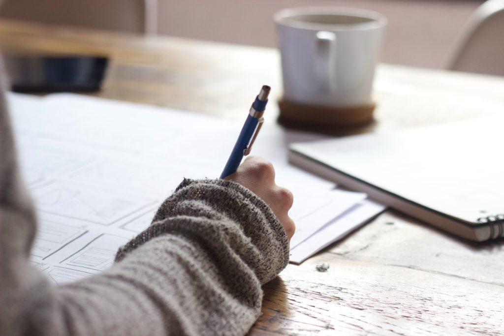 Et illustrasjonsbilde av en student som studerer. Det er notatblokk og ark på et bord, samt en kaffekopp.