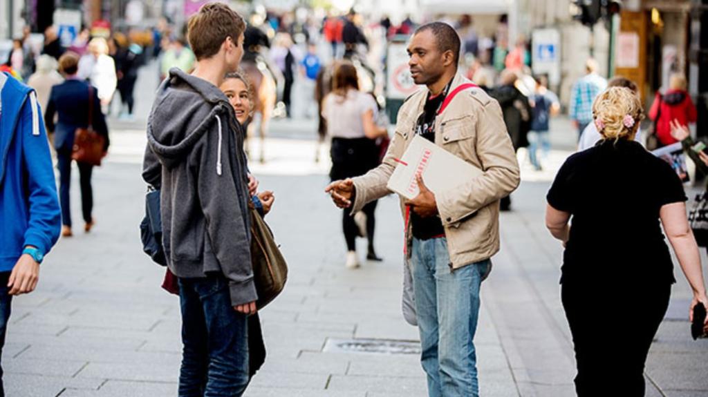 Et illustrasjonsbilde av en ansatt i en organisasjon som prøver å rekruttere nye støttespillere. Bilde er tatt ute på en gate i en storby.