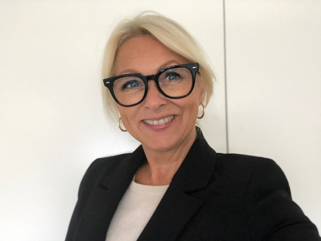 Portrett av Siri Nodland, generalsekretær i Norges Innsamlingsråd. Hun har på seg hvit genser med sort blazer over.
