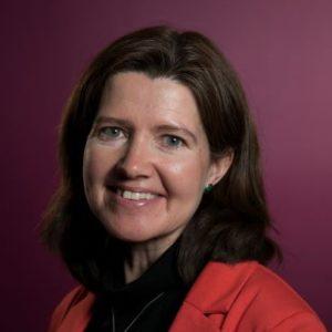 Portrettbilde av Siv Holthe Krogh, seniorrådgiver i Kirkens Nødhjelp. Hun har på sort genser med rød jakke over.