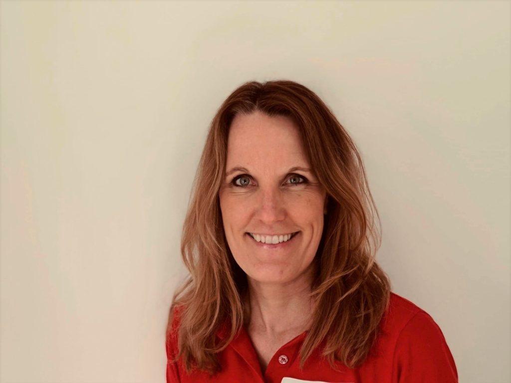 Portrettbilde av Nina Larsen, markedssjef i Norges Røde Kors. Hun har brunt langt hår og grønne øyne. På seg har hun en rød genser.