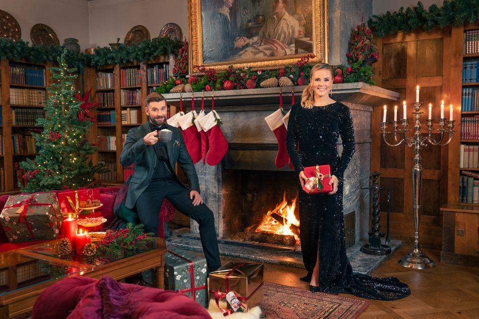 Senkvelds programledere, Stian Blipp og Helene Olafsen klare for Senkvelds Juledugnad. De har pyntet seg og står foran en peis med julegaver.