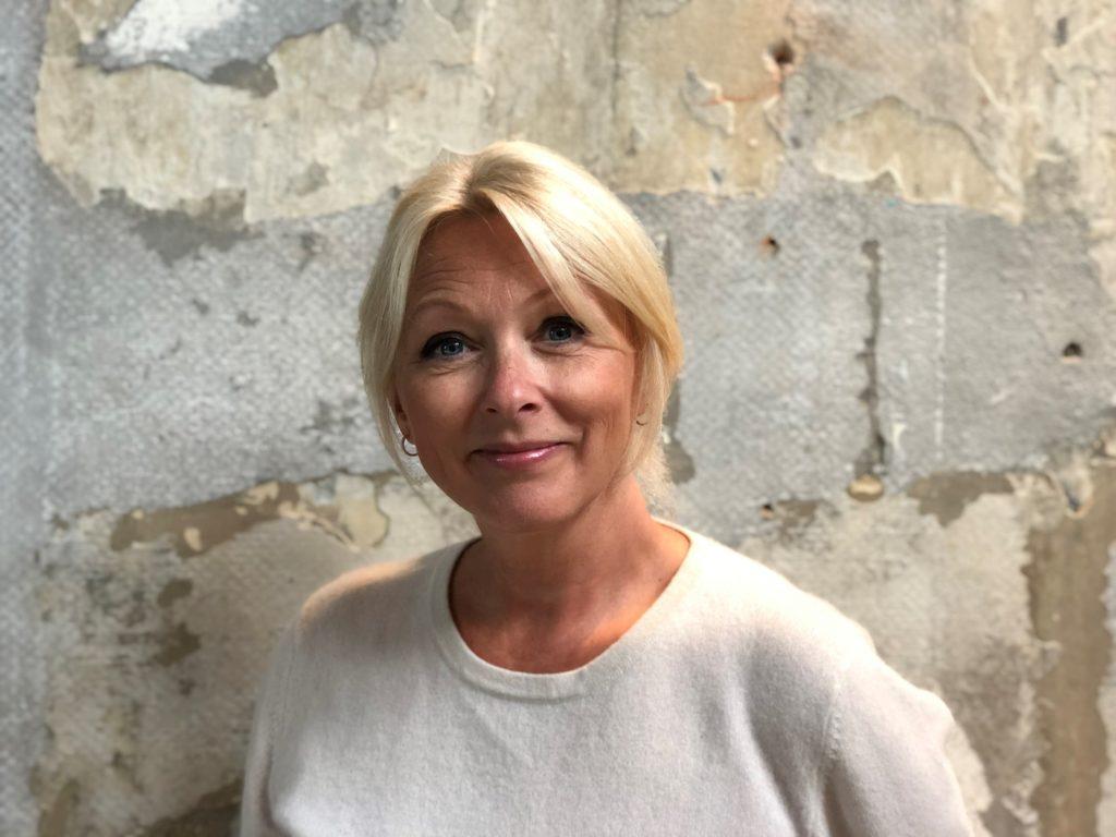 Portrettbilde av Siri Nodland, generalsekretær i Norges Innsamlingsråd. Hun har på seg en lys tynn strikkegenser og står mot en murvegg.