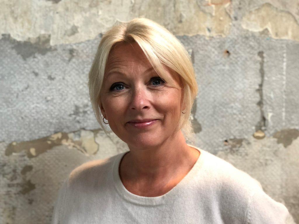 Portrettbilde av Siri Nodland, generalsekretær i Norges Innsamlingsråd. Hun har på seg lys genser og står mot en murvegg.