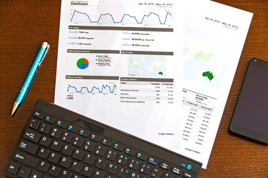 Det ligger rapporter med grafer på et bord som skal illustrere innsikt i tall over givermarkedet. Det ligger også en penn, en mobil og et tastatur på bordet.
