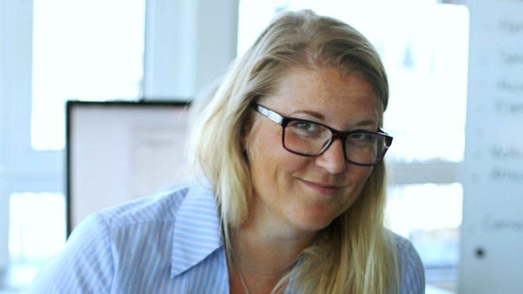 Portrettbilde av Ane Tollerød Fosse. Hun har på seg mørke briller og en blå skjorte.