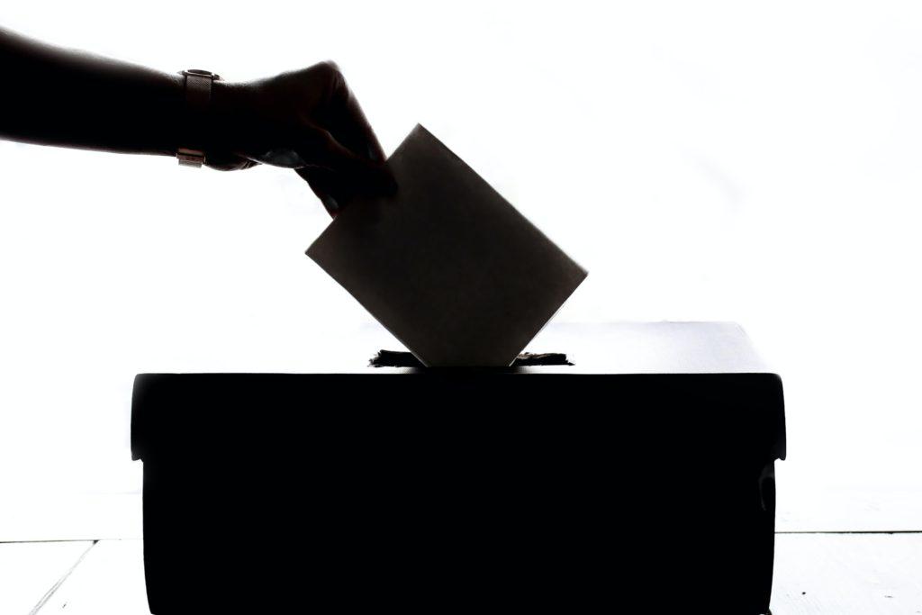 Et illustrasjonsbilde av en dame som legger en stemmeseddel i en lukket stemmeboks.
