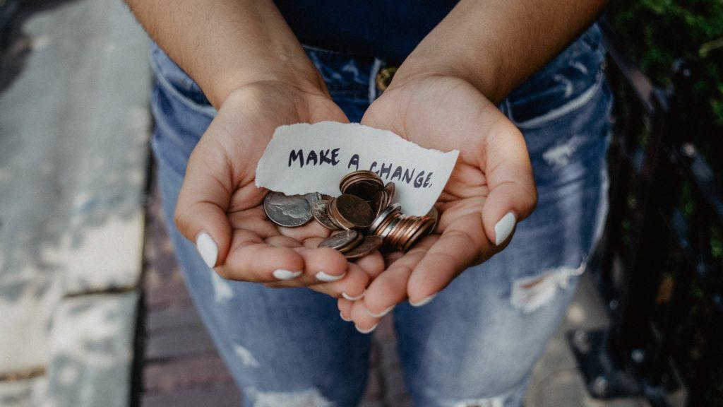 """En dame holder frem sine hender. Hun viser frem penger og en lapp med teksten """"make a change"""" for å illustrere at en donasjon til en organisasjon kan gjøre en forskjell i verden."""