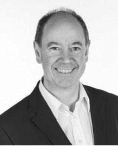 Portrettbilde av Knut Nordenhaug. Han har på seg sort jakke med hvit skjorte under. Bildet er i sort/hvitt.