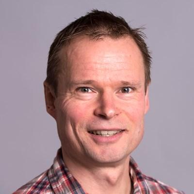 Portrettbilde av Leif Hem, professor ved Norges Handelshøyskole. Han har på seg rødrutete skjorte, og smiler mot kameraet.