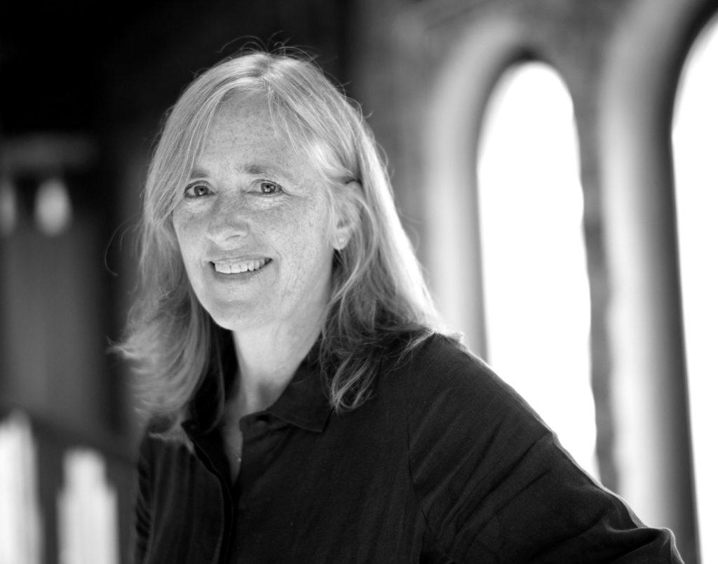 Portrettbilde av Charlotte Arnø Storebakken, fagansvarlig i Fundraising Norge. Hun har på seg sort bluse og står foran et vindu. Bildet er i sort/hvitt.