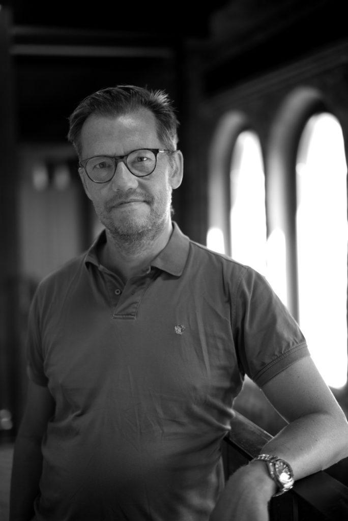 Portrettbilde av Klaus Damlien, styreleder i Fundraising Norge. Han har kort hår og bruker mørke briller. Klaus står foran et vindu. Bildet er i stort/hvitt.