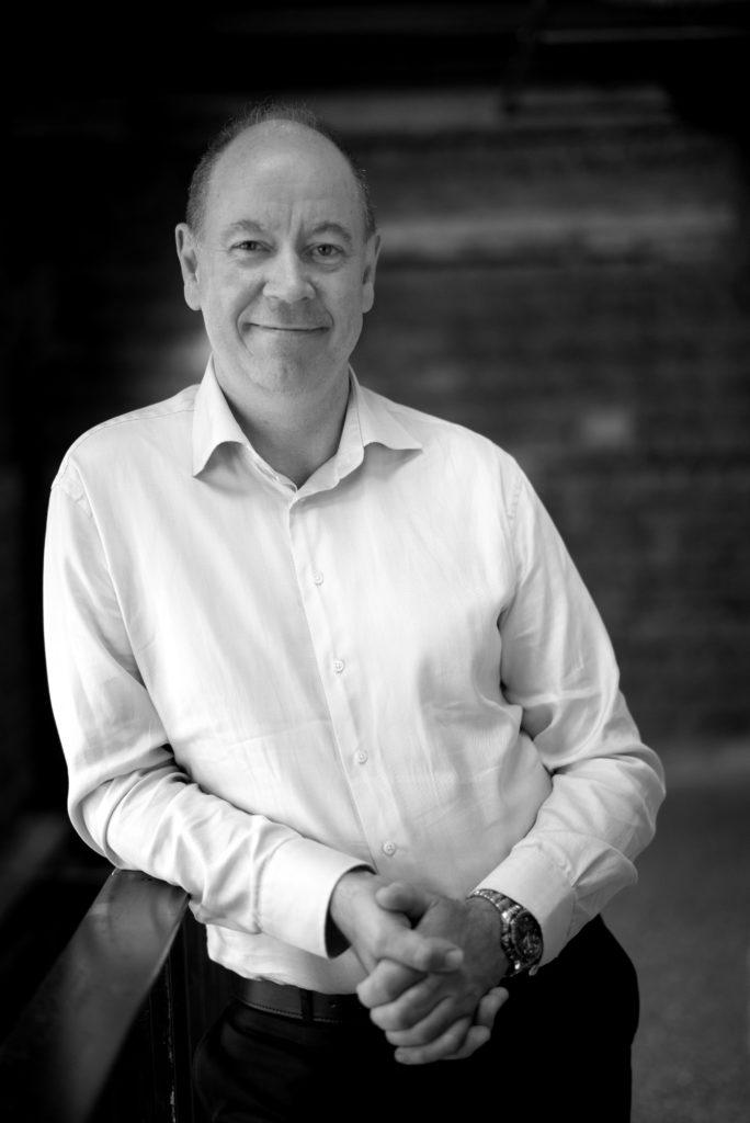 Portrettbilde av Knut Nordenhaug, styremedlem i Fundraising Norge. Han har på seg en hvit skjorte og mørk dressbukse. Knut står foran et vindu. Bildet er i stort/hvitt.
