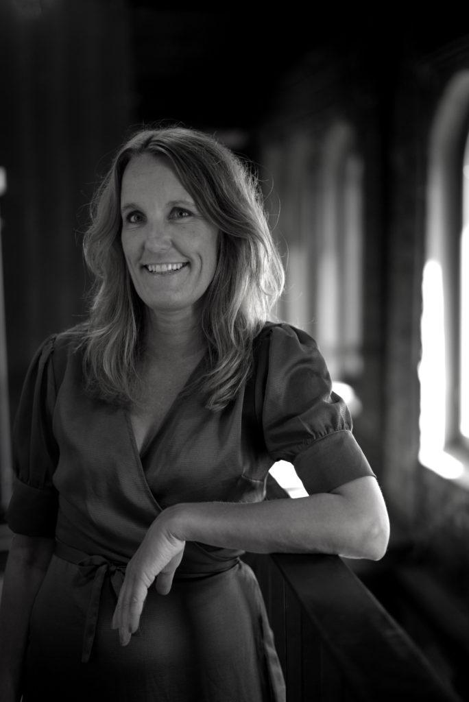 Portrettbilde av Nina Larsen, styremedlem i Fundraising Norge. Hun har mørkt hår og på seg en kjole. Nina står foran et vindu. Bildet er i stort/hvitt.