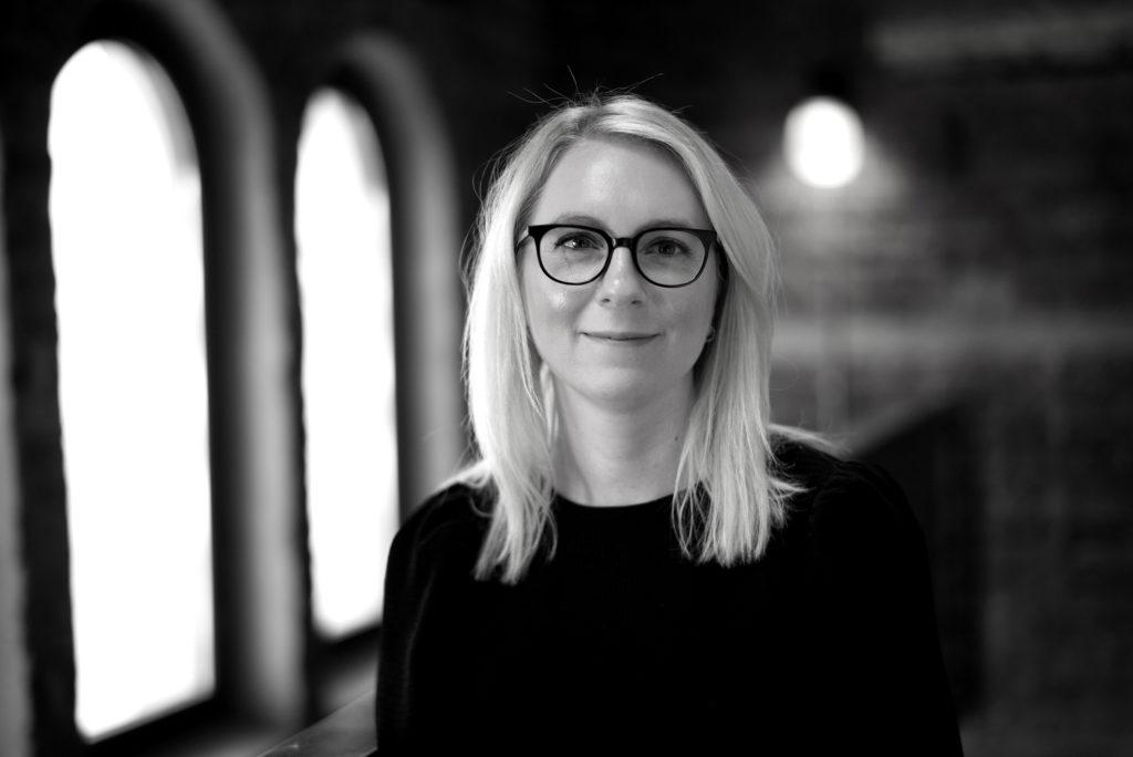 Portrettbilde av Rikke Solberg, kommunikasjonsansvarlig i Fundraising Norge. Hun har på seg sort bluse og står foran et vindu. Bildet er i sort/hvitt.