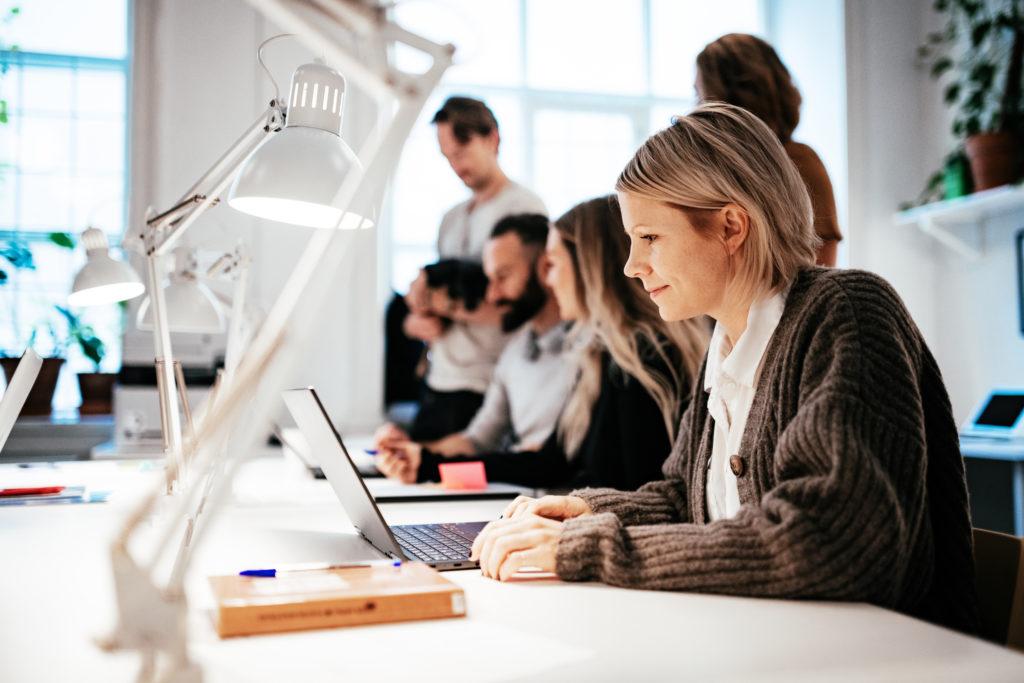 Illustrasjonsbilde av flere voksne som sitter og studerer ved et bord.