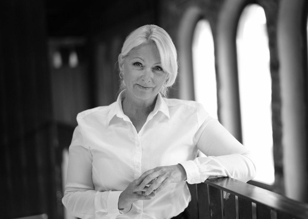 Portrettbilde av Siri Nodland, generalsekretær i Fundraising Norge. Hun har på seg hvit skjorte og står foran et vindu. Bildet er i sort/hvitt.