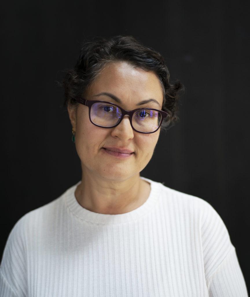 Portrettbilde av Frøydis Johannessen, politisk rådgiver i Fundraising Norge. Hun har på seg hvit overdel og står mor en sort bakgrunn.