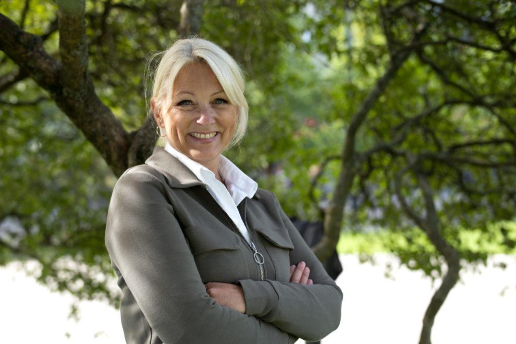 Siri Nodland, generalsekretær i Fundraising Norge. Hun har på seg en hvit skjorte og grønn jakke. Siri står under et tre utenfor Stortinget.